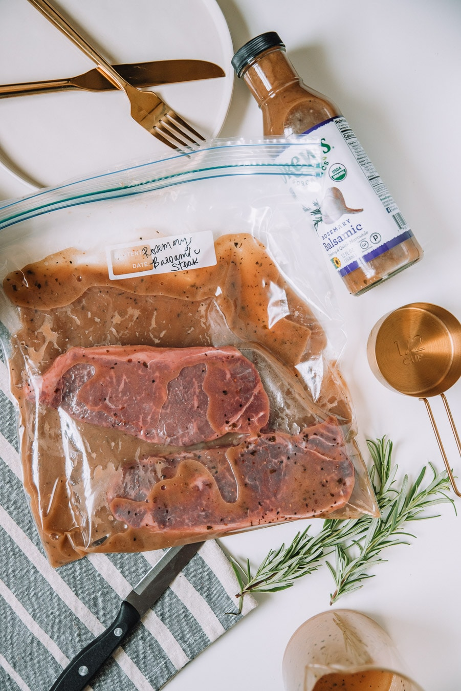 Steaks in a plastic bag marinating on a white table.