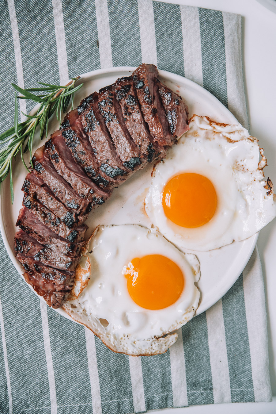 Rosemary steak and eggs on a white plate