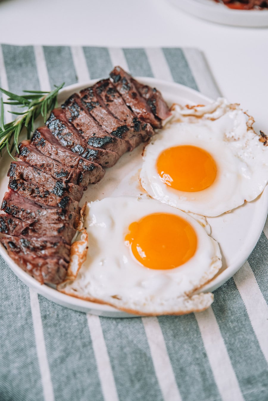 Rosemary Balsamic steak and Eggs on a white plate.