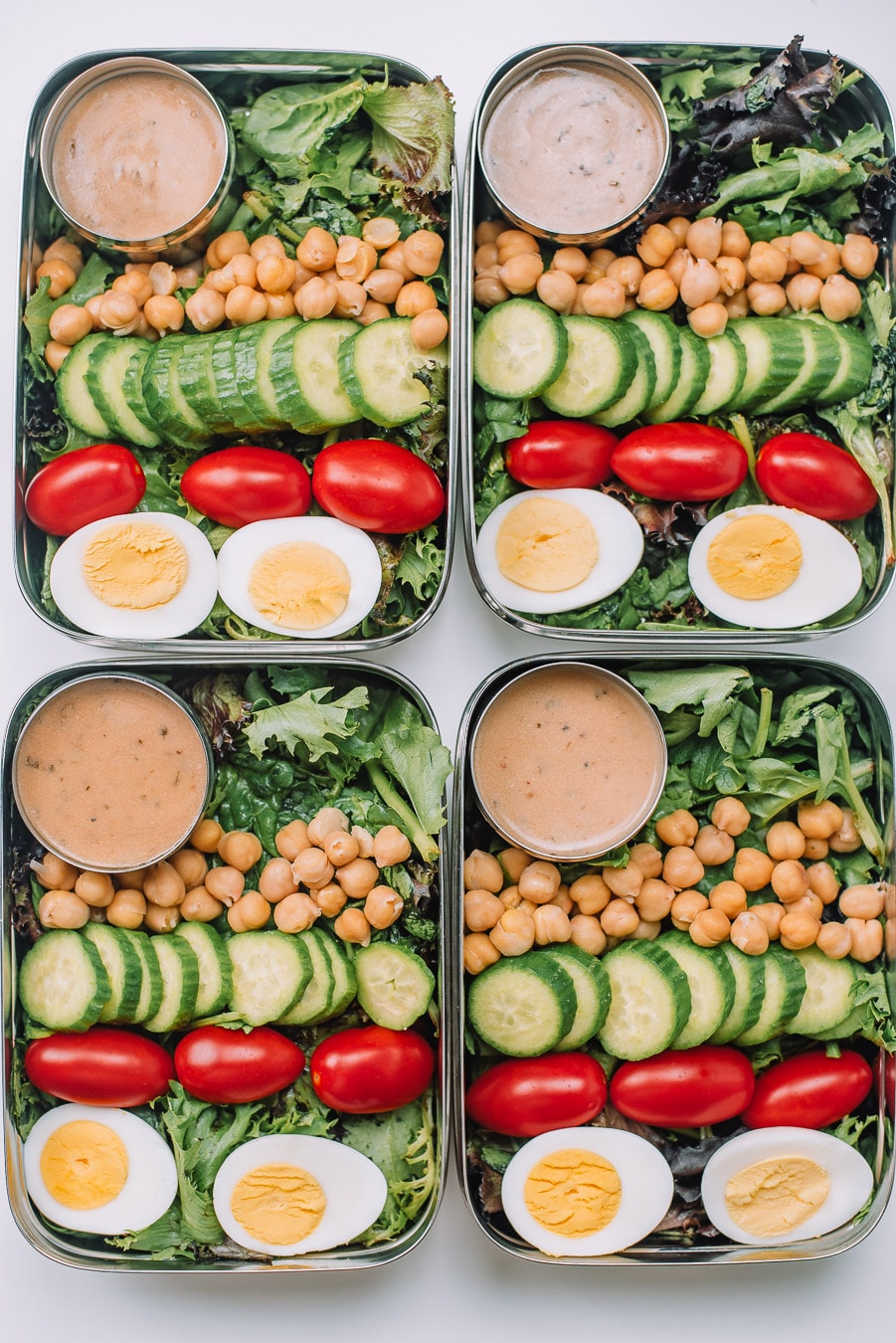 4 Bento boxes filled with mixed greems, boiled egg, grape tomatoes, mini cucumbers, chickpeas, and Drew's Organics Tahini Goddess Dressing and Marinade