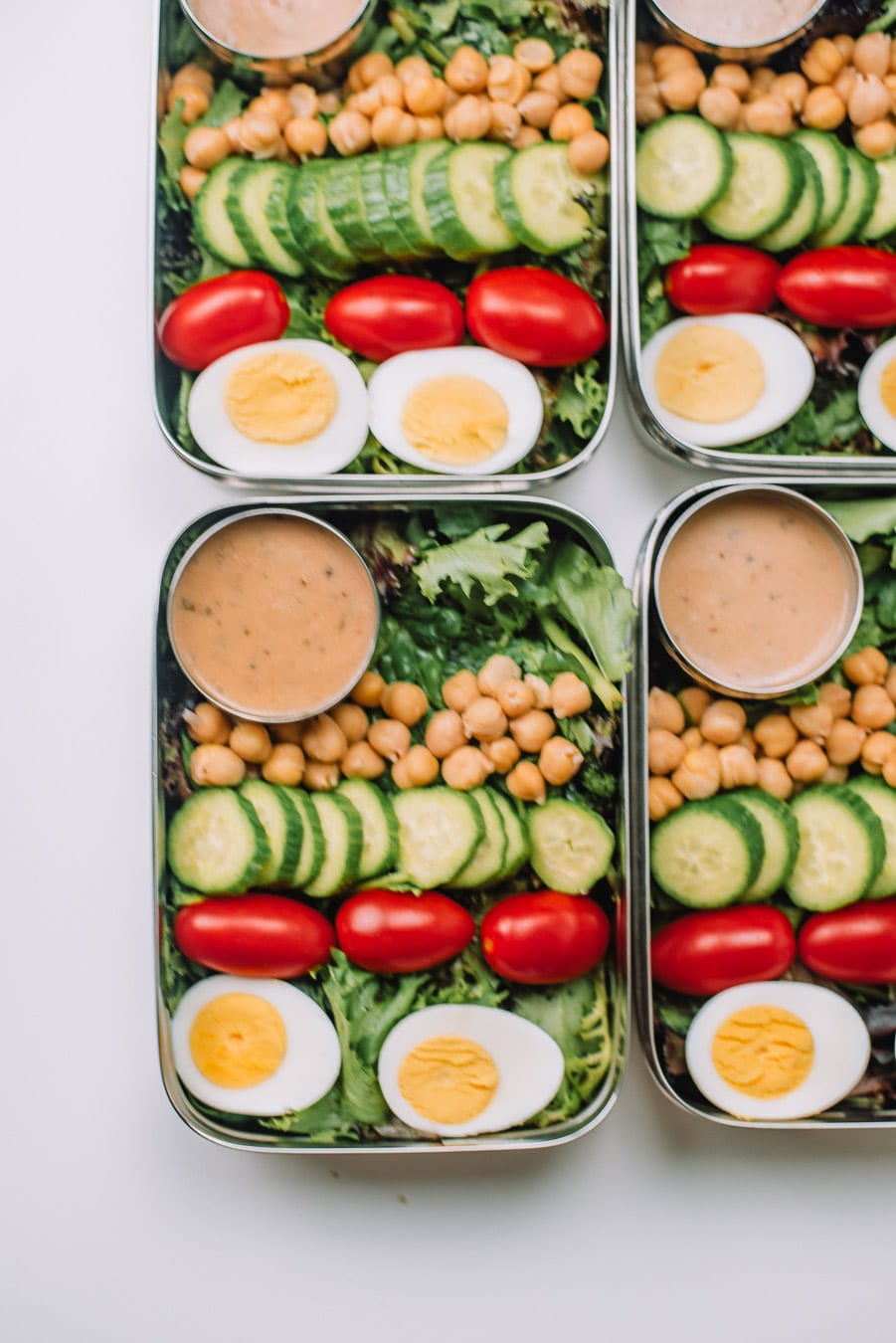 4 Bento boxes filled with mixed greens, boiled egg, grape tomatoes, mini cucumbers, chickpeas, and Drew's Organics Tahini Goddess Dressing and Marinade