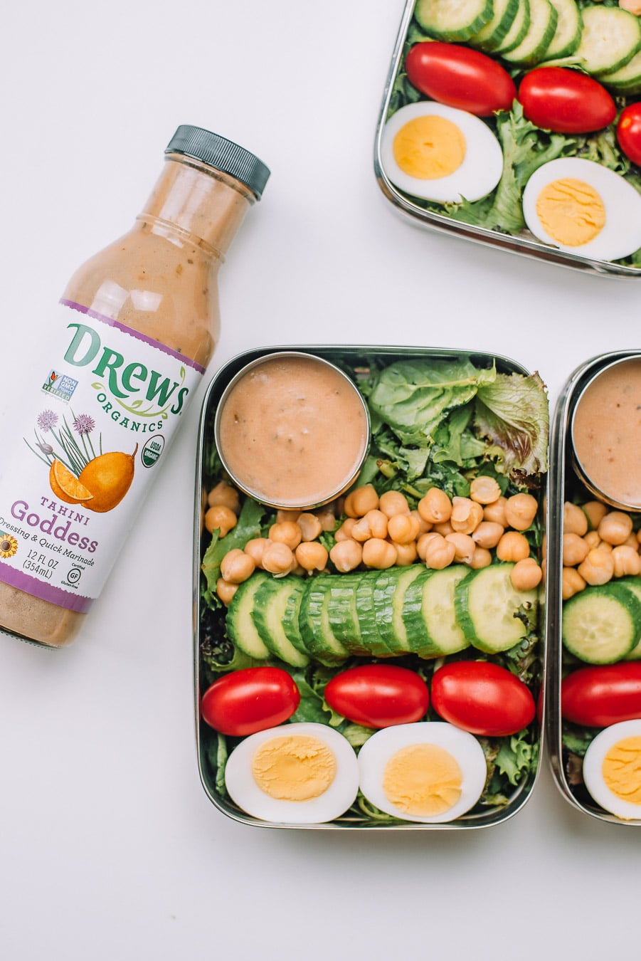3 Bento boxes filled with mixed greens, boiled egg, grape tomatoes, mini cucumbers, chickpeas, and Drew's Organics Tahini Goddess Dressing and Marinade with bottle of dressing