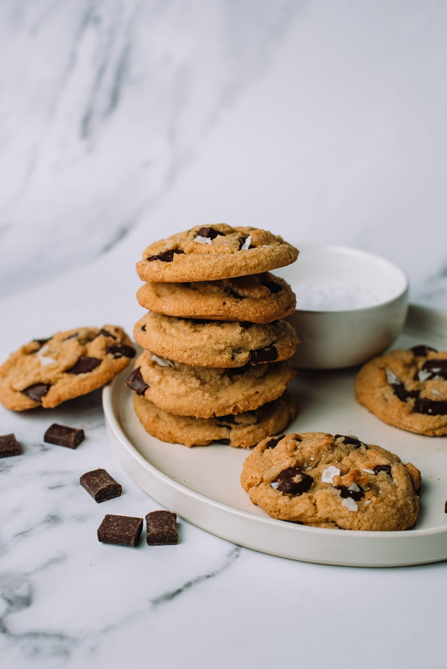 Olive Oil Chocolate Chip Cookies stacked on top of each other on a white plate with extra chocolate morsels.