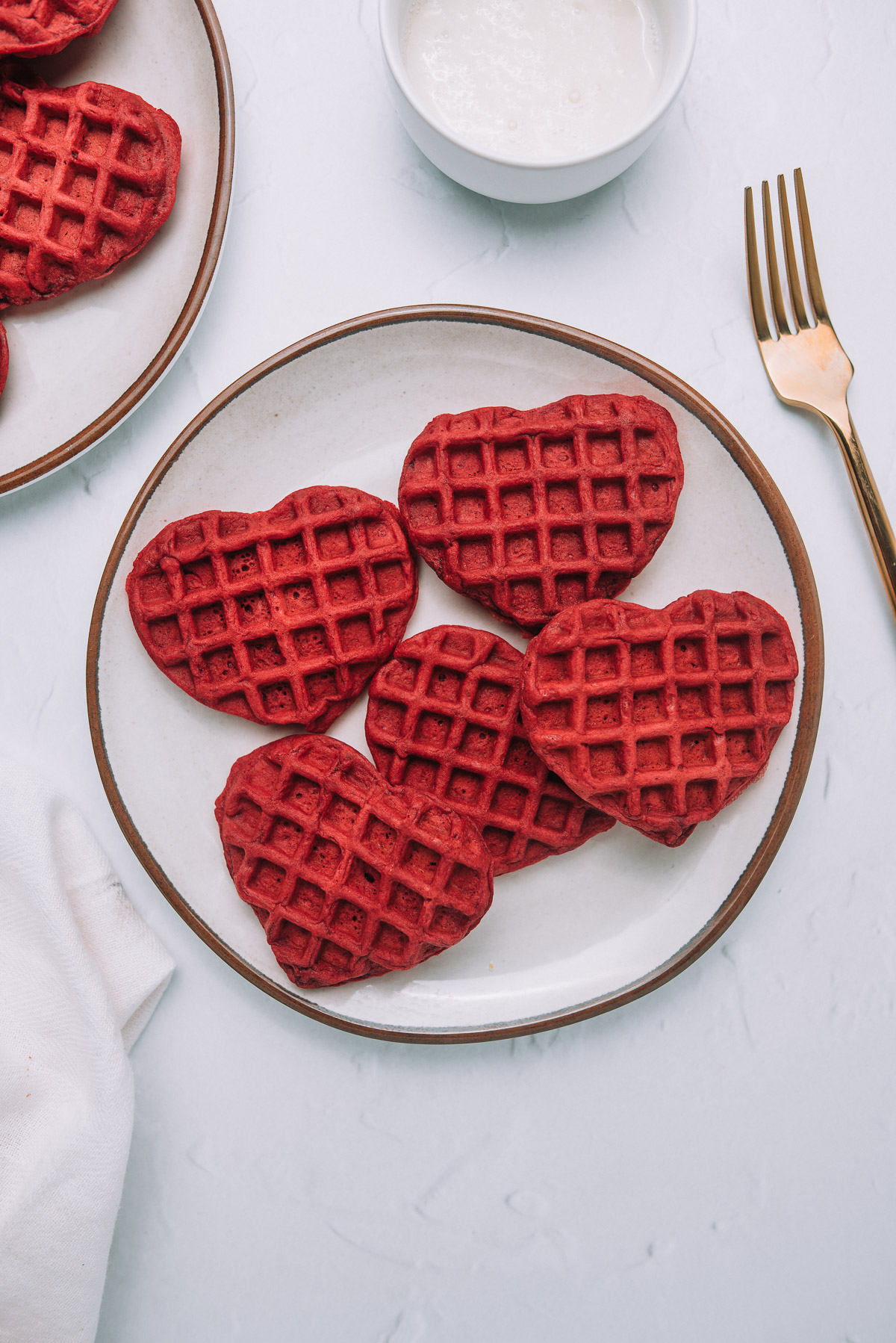 Buttermilk Red Velvet Waffles on a plate sitting on a white table with a gold fork.