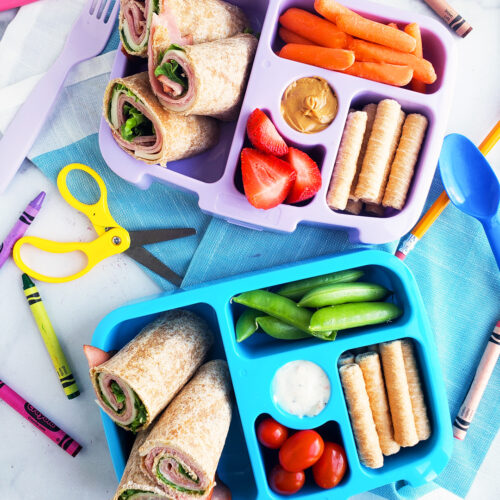 Bento box filled and arranged beautifully with fruits, veggies, whole wheat ham and cheese wraps. Healthy bento lunch ideas for kids. Littleeatsandthings.com