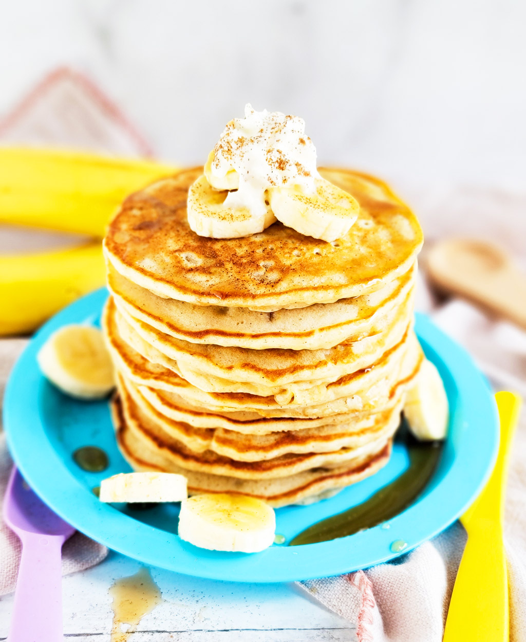banana pancakes with syrup topped with sliced bananas, whipped cream, and cinnamon  littleeatsandthings.com