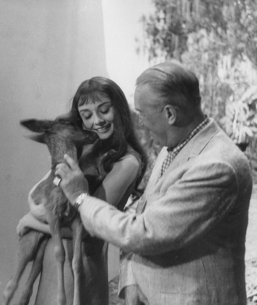 Hepburn is shown holding a fawn in this lovely