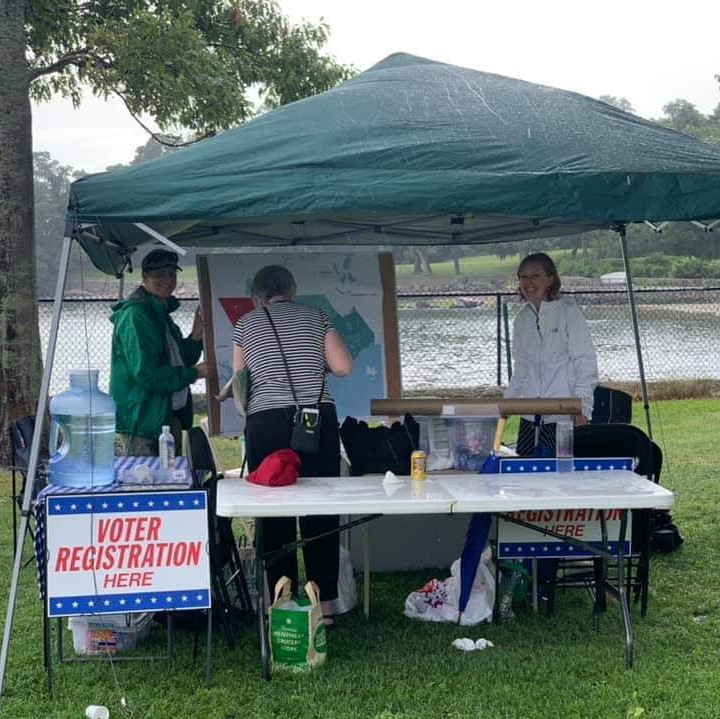 Photo of Hannah Bowen and two other volunteers in a tent at Beverly Homecoming Lobster Fest with a sign reading Voter Registration Here.