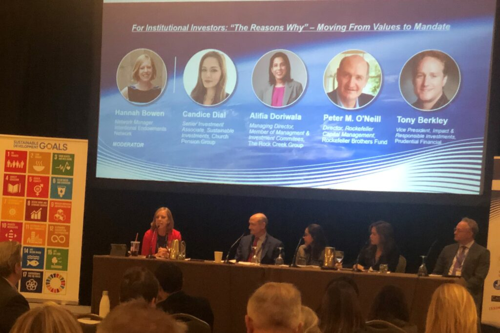 Photo of Hannah Bowen moderating a panel at a conference about sustainable investing