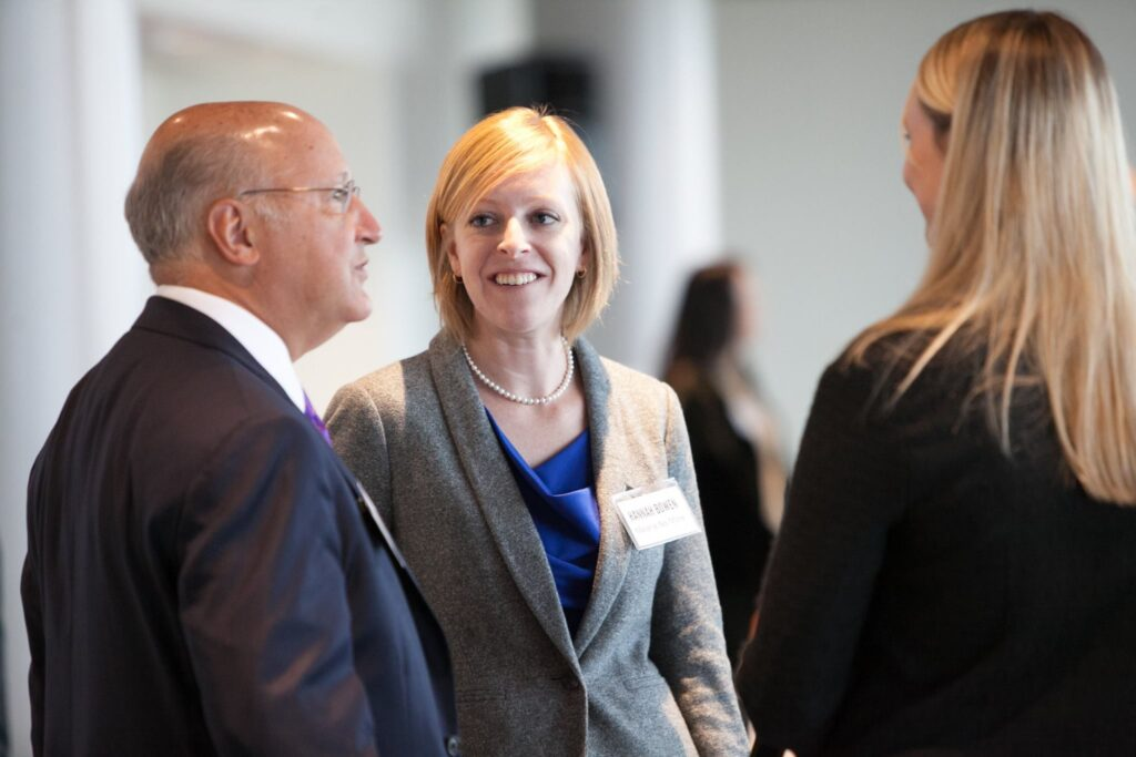 Photo of Hannah speaking with colleagues in business attire at an advocacy event
