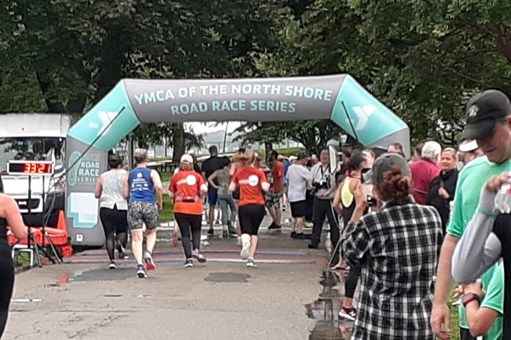 Photo of Hannah crossing the finish line of the YMCA 5k road race along with other runners