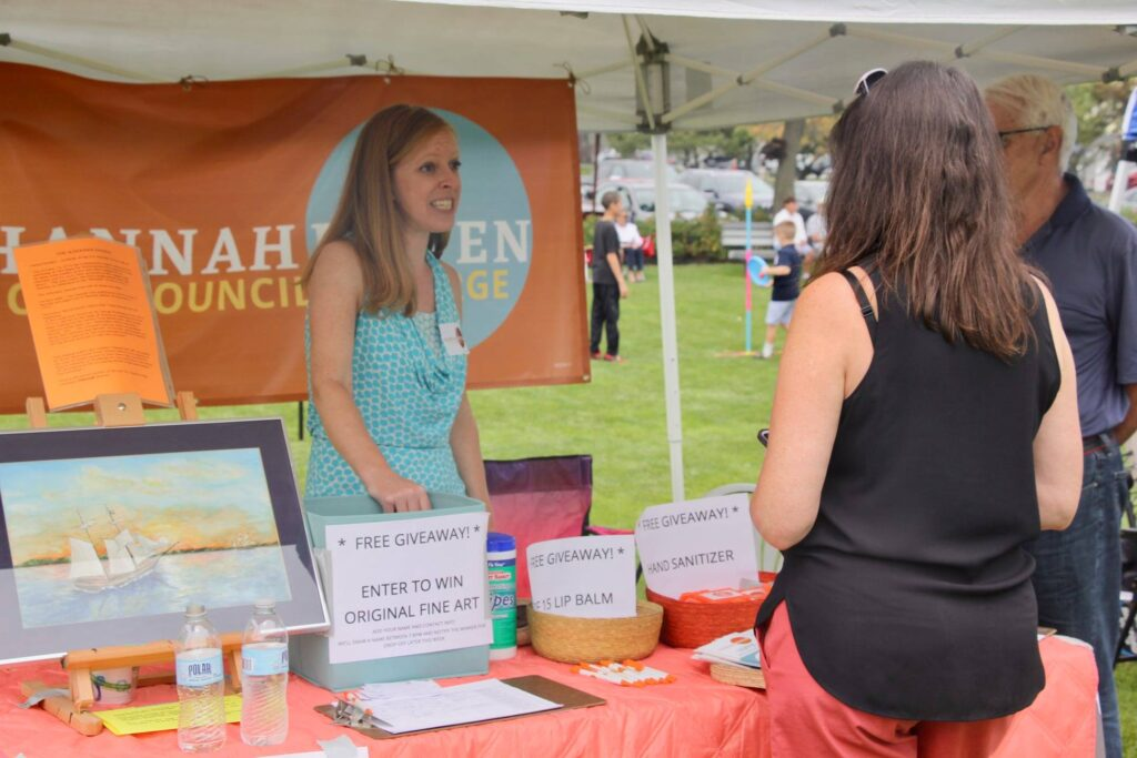 Photo of Hannah speaking to a visitor to the campaign tent at an outdoor event