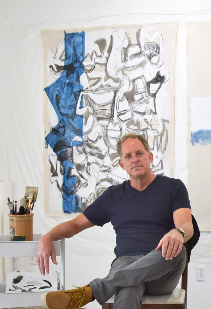 Toby Hill sitting in front of his artwork