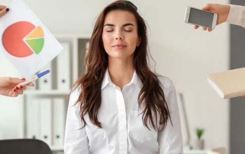 black hair girl sitting at an office table and doing meditation