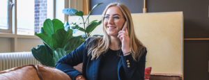 blond hair girl sitting in bed and talking on the phone and smiling