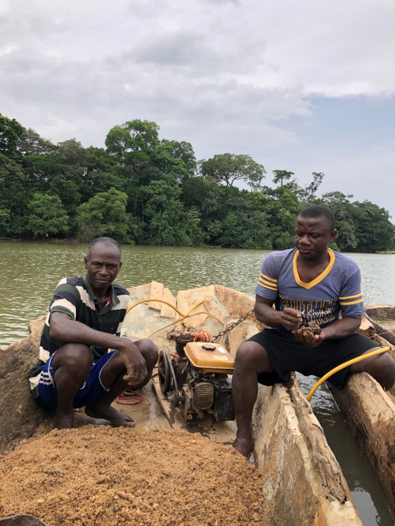 Umaru and Ibrahim on a canoe with recovered gravel from the Sewa river.