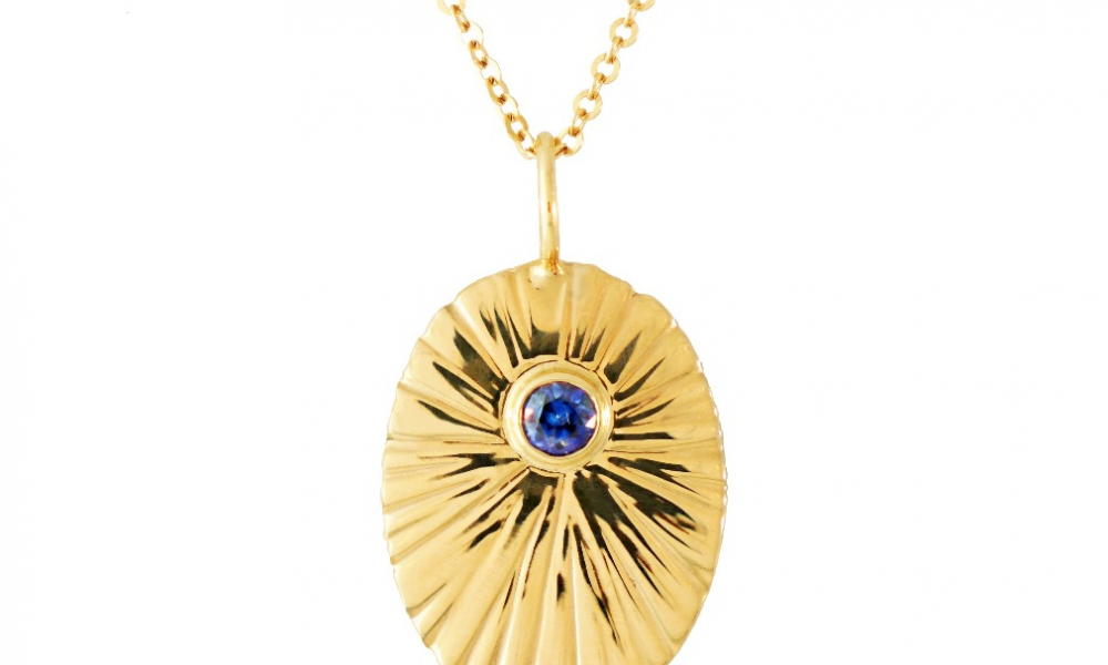 Starburst Charm necklace in 14k and 18k yellow gold with a blue sapphire accent, $1,130; available online at Lauren Chisholm
