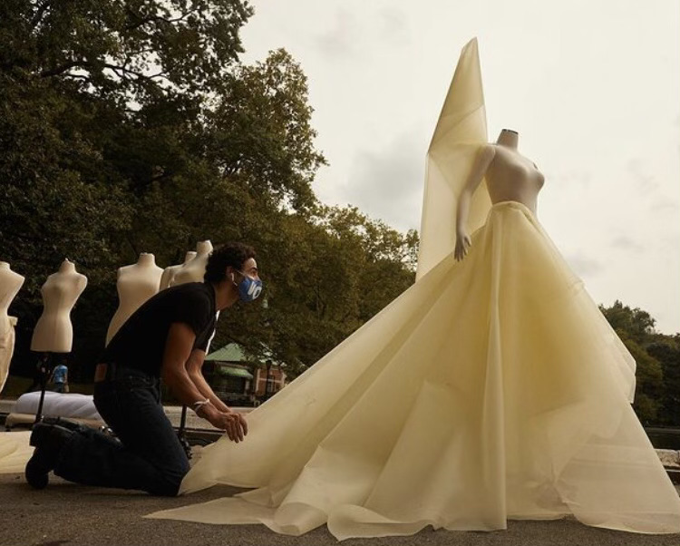 Couture designer Zac Posen drapes fabric on a dress form in Central Park; the drapes are created with pins and the positions are inspired by New York City.