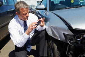 Insurance Adjuster Inspecting a Damaged Car