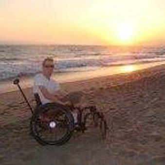 A man on a wheelchair in the beach