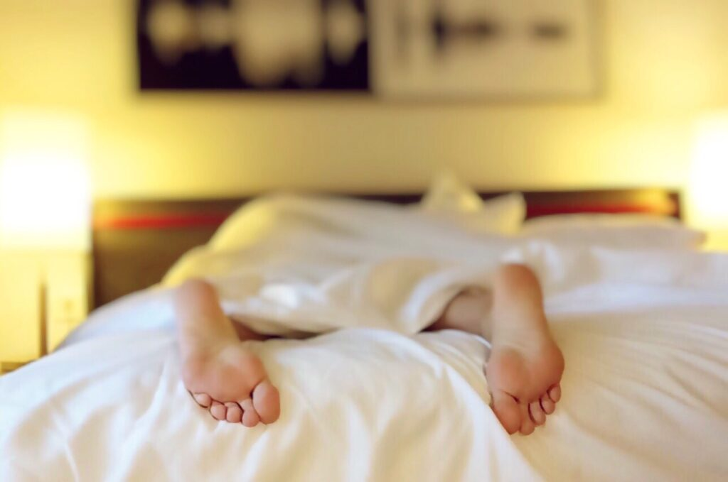 Feet of a sleeping person on the bed