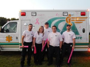 Community Care Ambulance Paramedics in front of an ambulance.