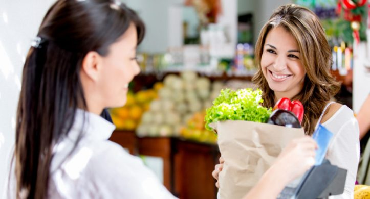 smiling girl checking out in grocery store