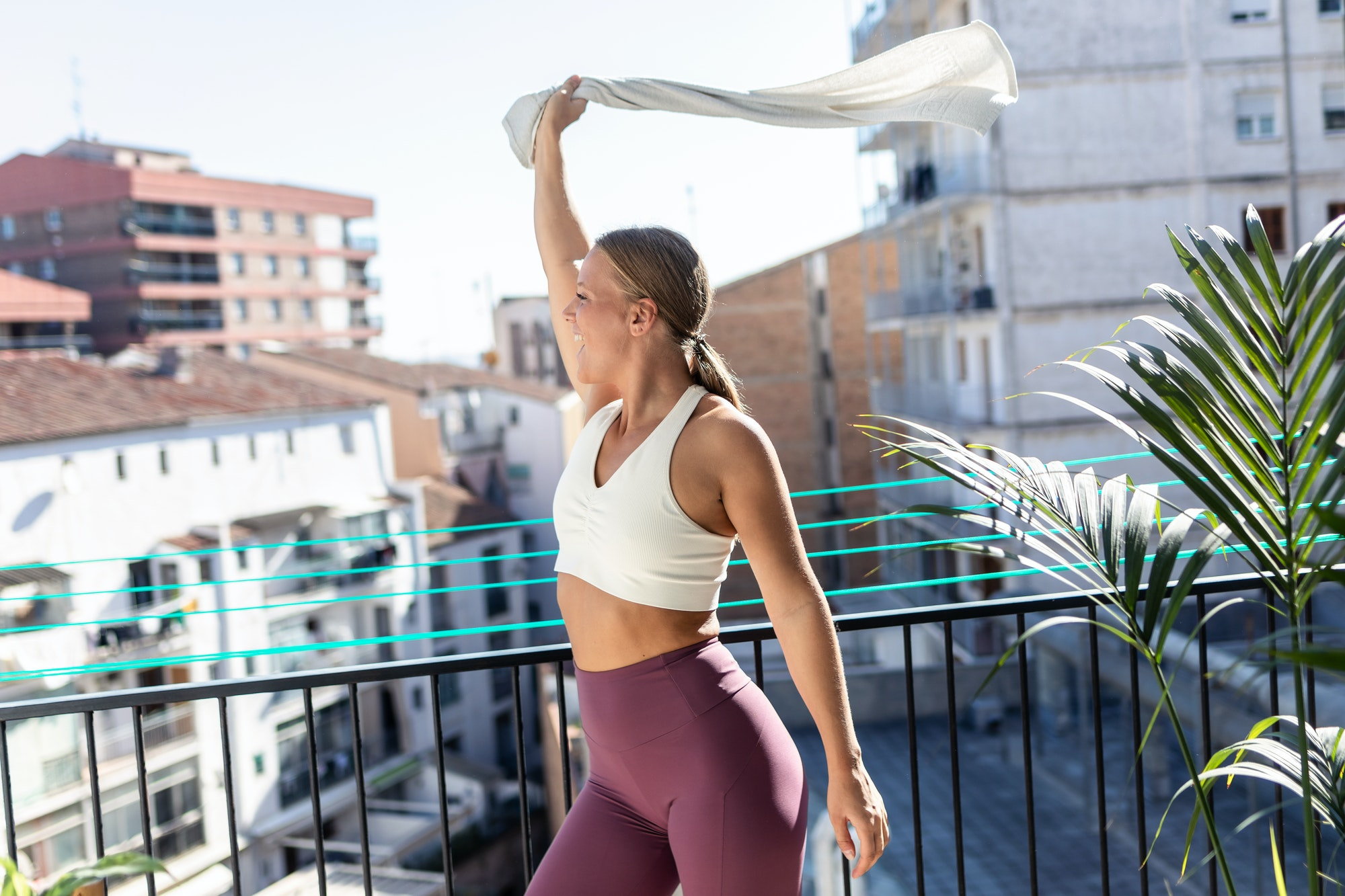Sporty happy woman greeting effusively with towel to a neighbor while standing in balcony at home.