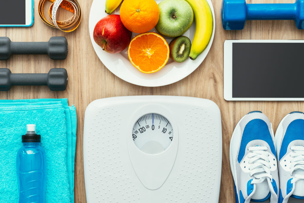overhead shot of weight scale, water bottle, running shoes, fruit, and dumbells