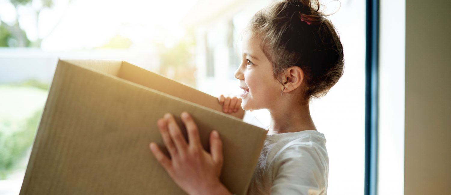 Young girl holding a large cardboard box.