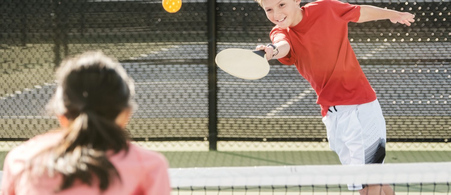 A young boy and girl playing pickleball against each other outside on a pickleball court.