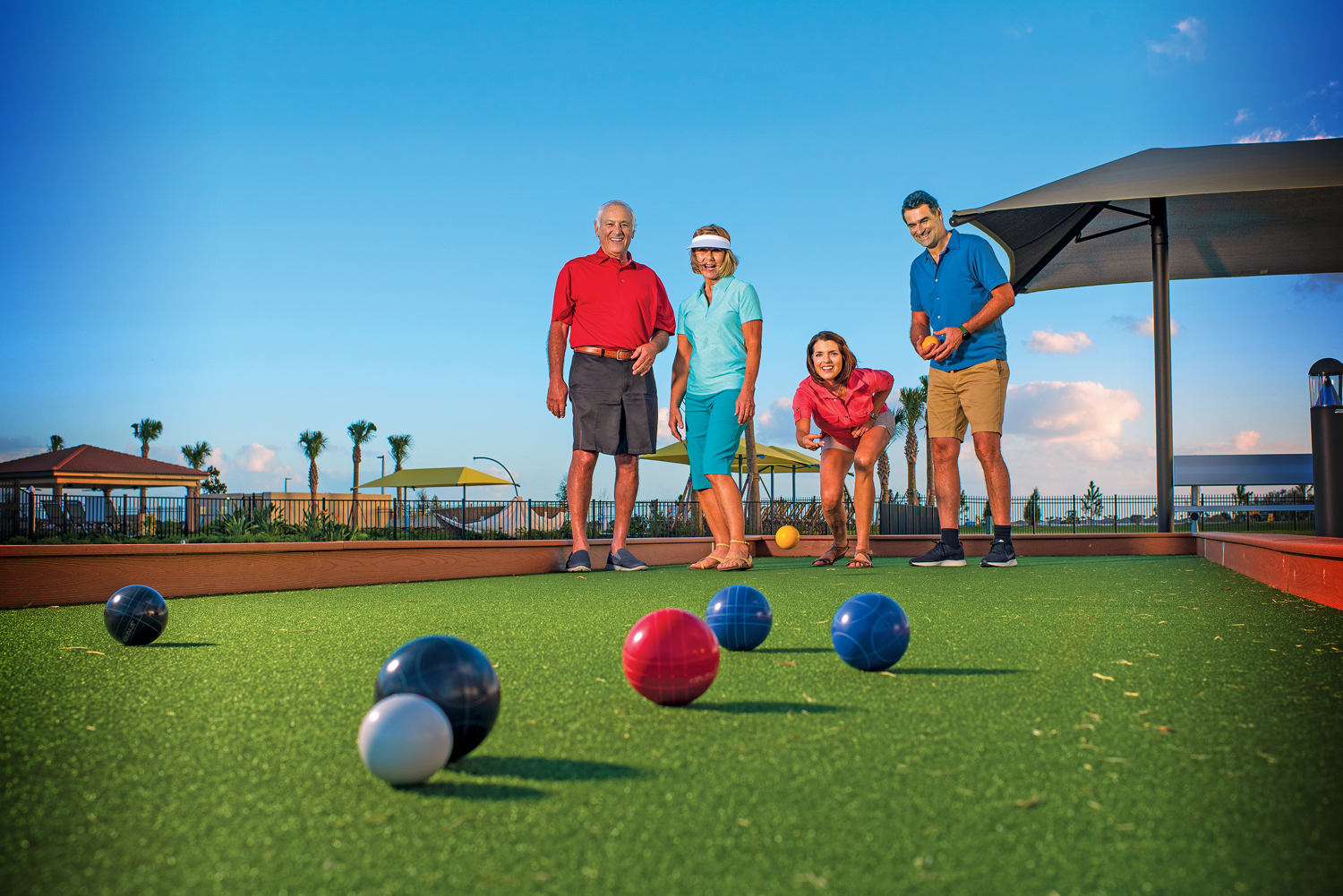 Two couples playing bocce ball.