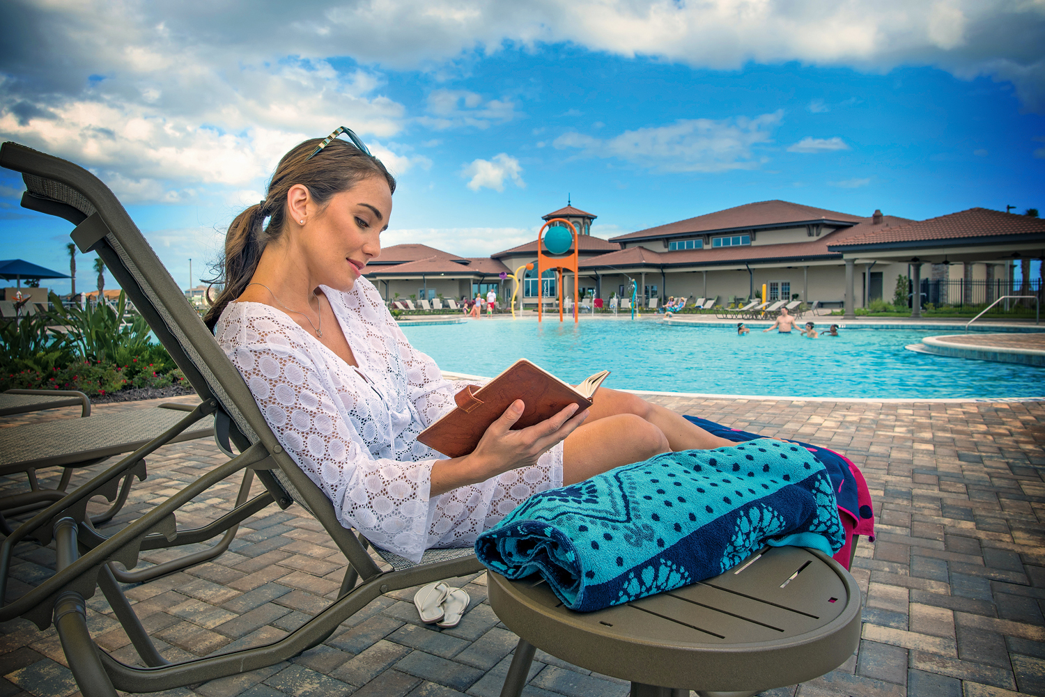 Woman reading on lounge chair next to family pool.