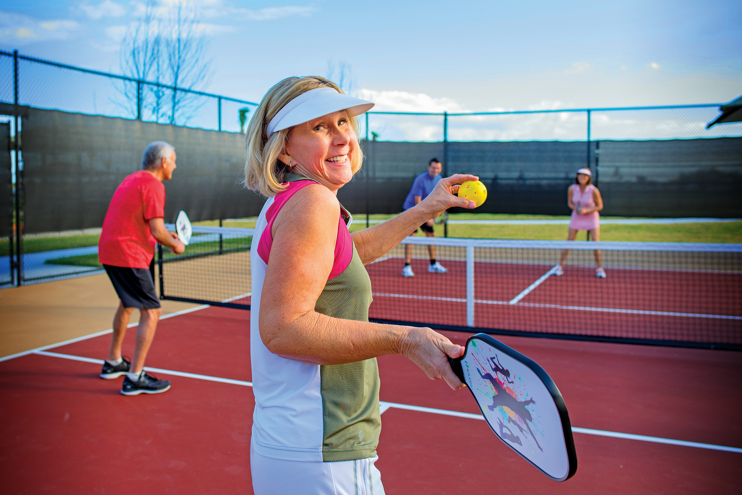 Woman playing pickleball holding racquet with 3 people smiling at camera.