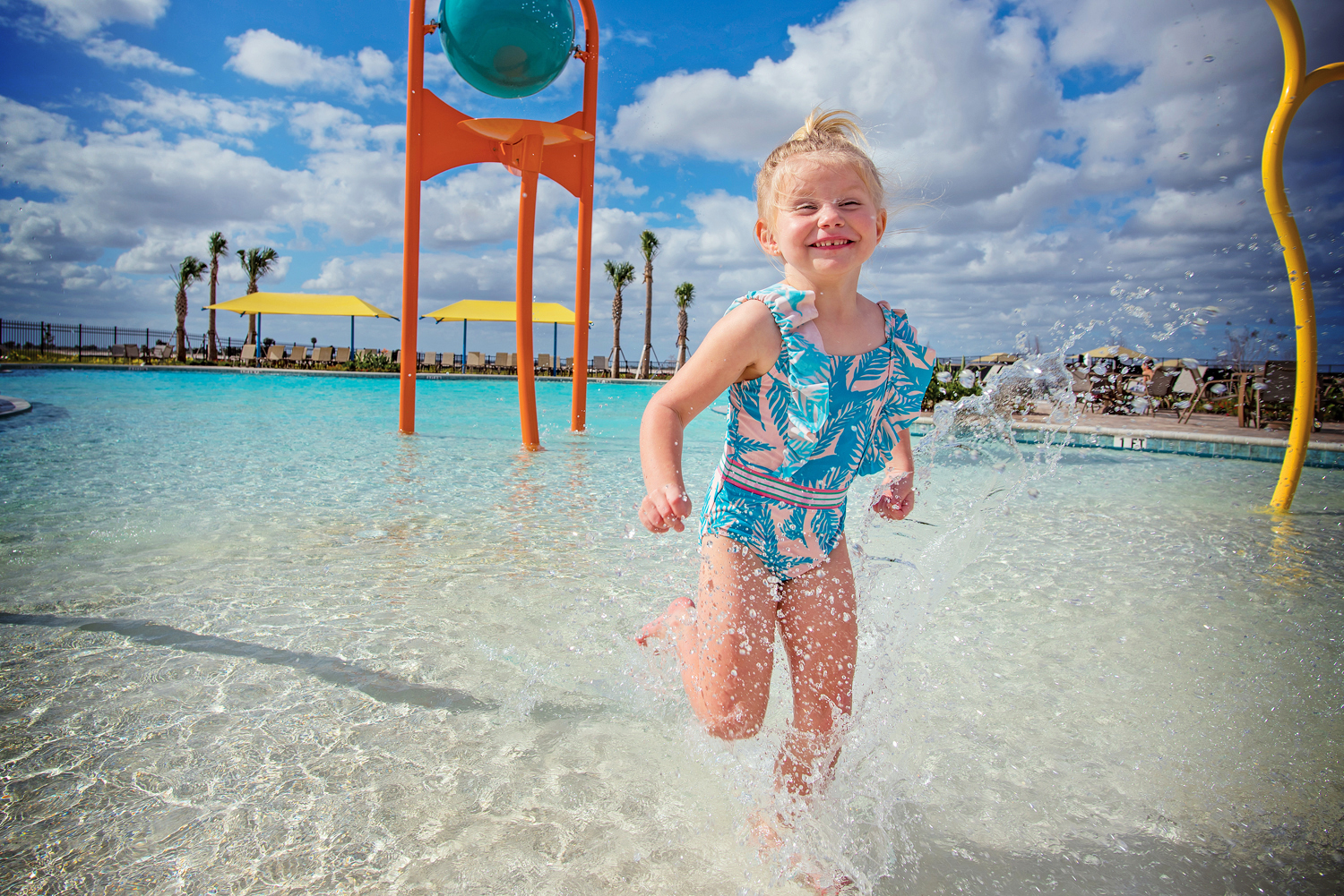 Young girl running in splash park in pool.
