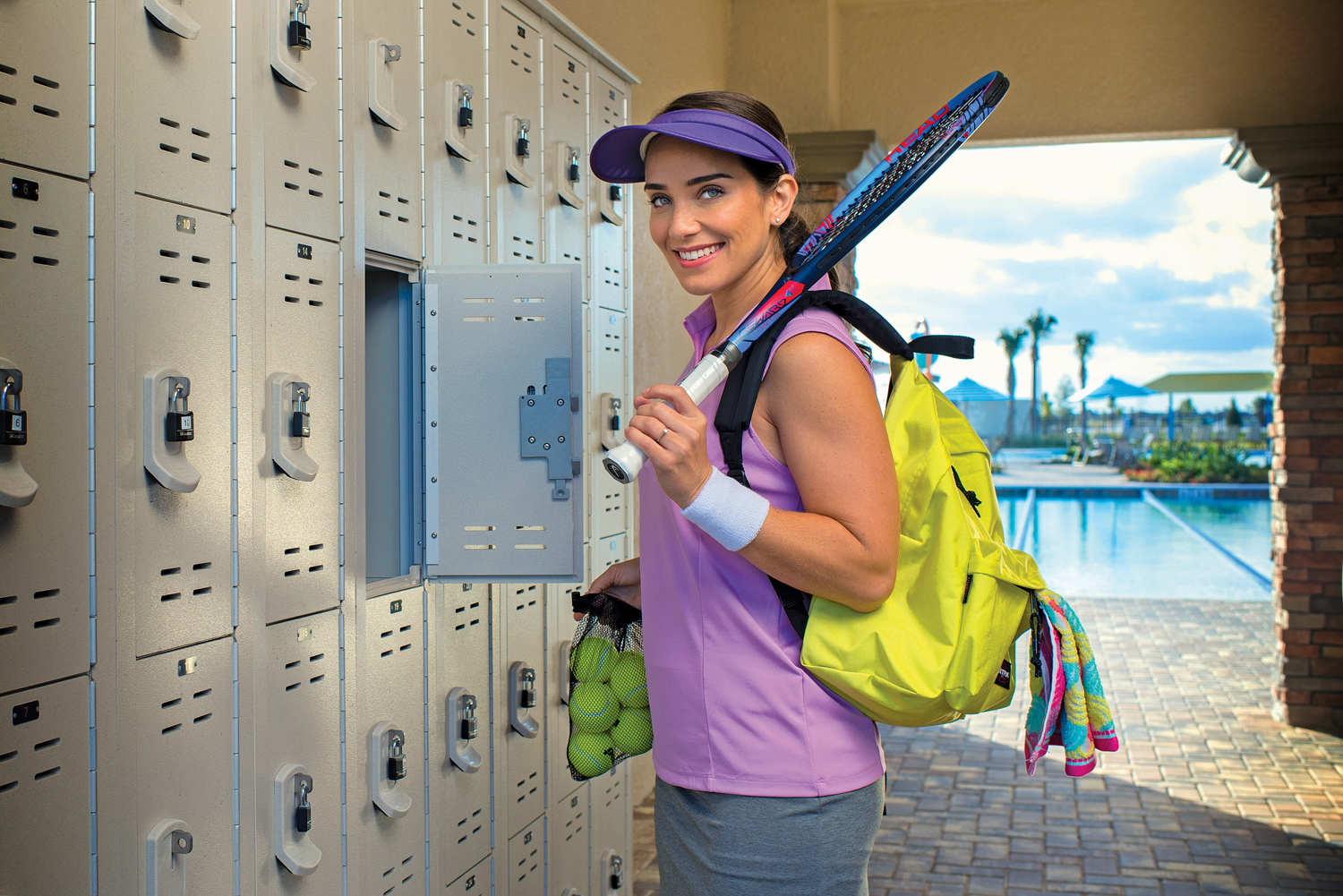 Woman with tennis gear at outdoor lockers.