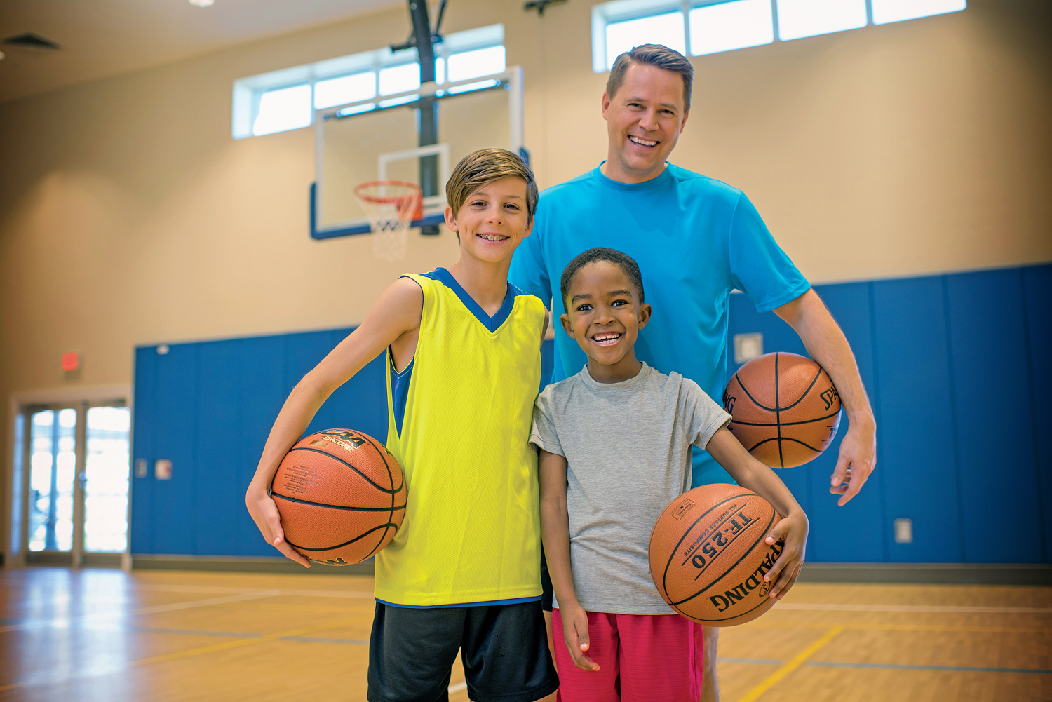 A man and two boys with basketballs smiling and posing for camera.