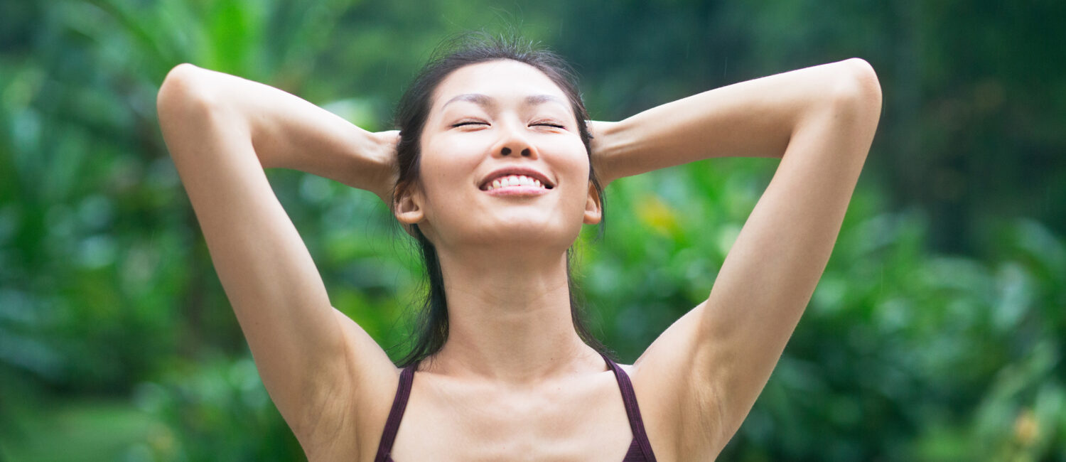 Asian woman with arms raised and eyes closed enjoying nature in park