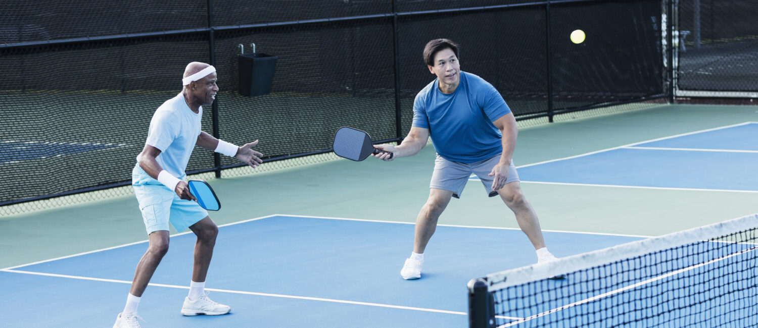 Two multi-ethnic senior men playing pickleball. They are a doubles team. The African-American man, in his 70s, is watching as his partner, an Asian man in his 60s, gets ready to hit the ball with his paddle.