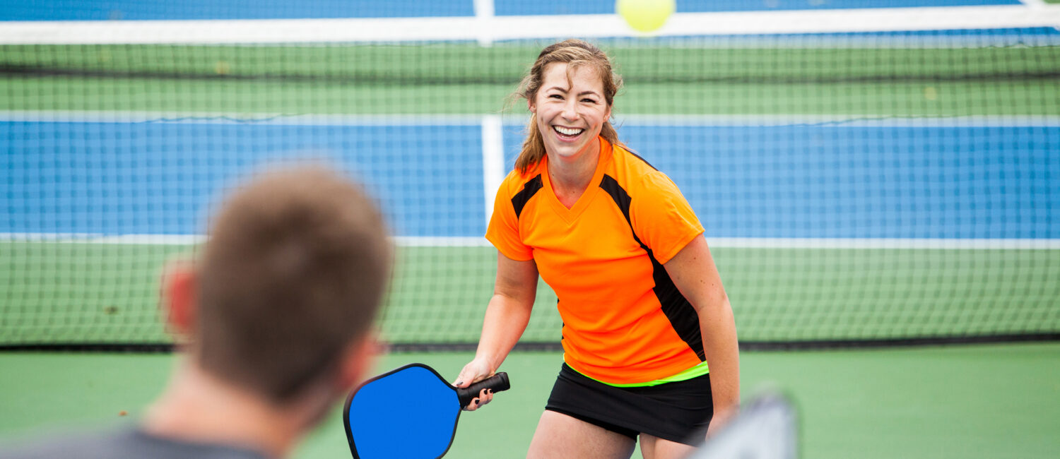 Female Pickleball player is returning a serve on an outdoor court.