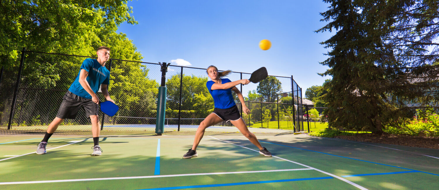 A Caucasian young woman and a young man playing double in pickleball in a pickleball court. Pickleball, one of the faster growing sport in the United States. Photographed in action in horizontal format.