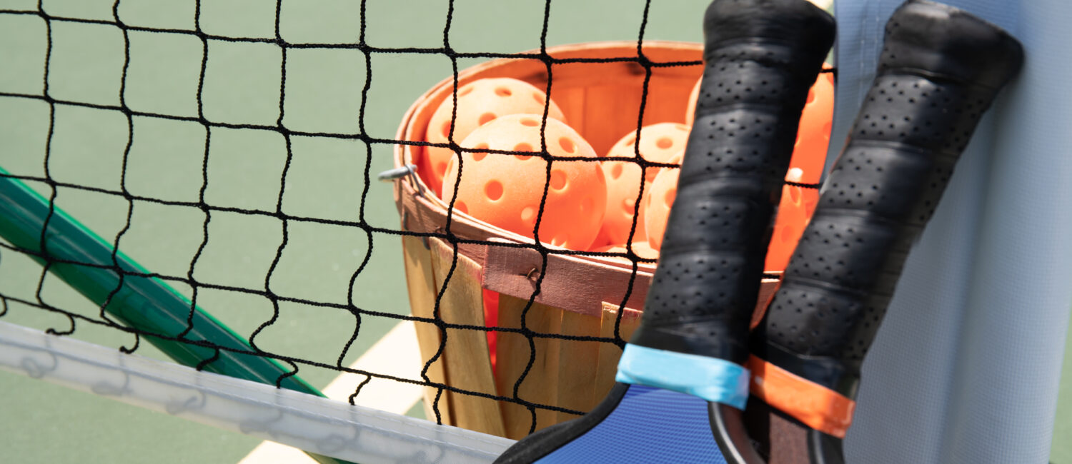 A basket of pickleballs and two paddles on a court laying against the net.