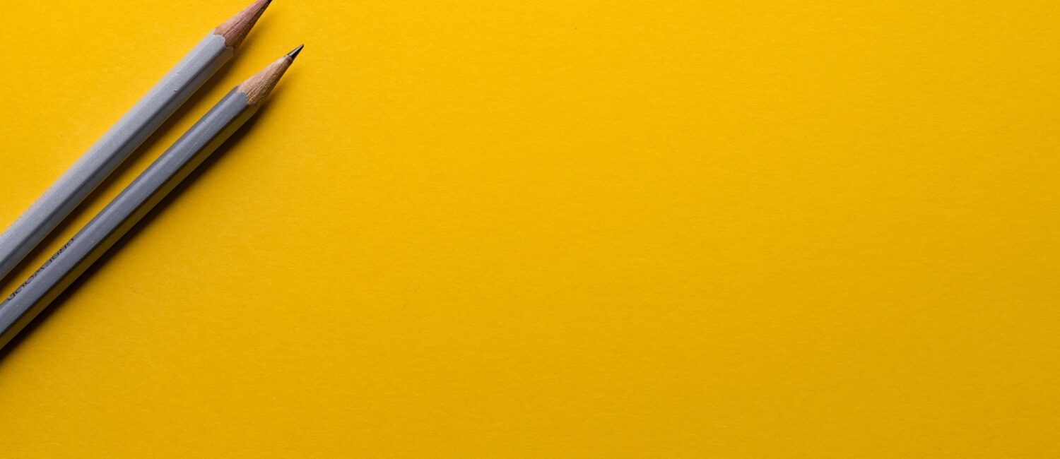 Two number two pencils on a bright yellow background.