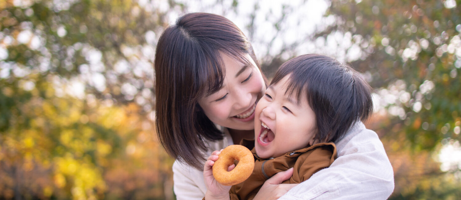 Young mother and son eating doughnut in public park with full of fun