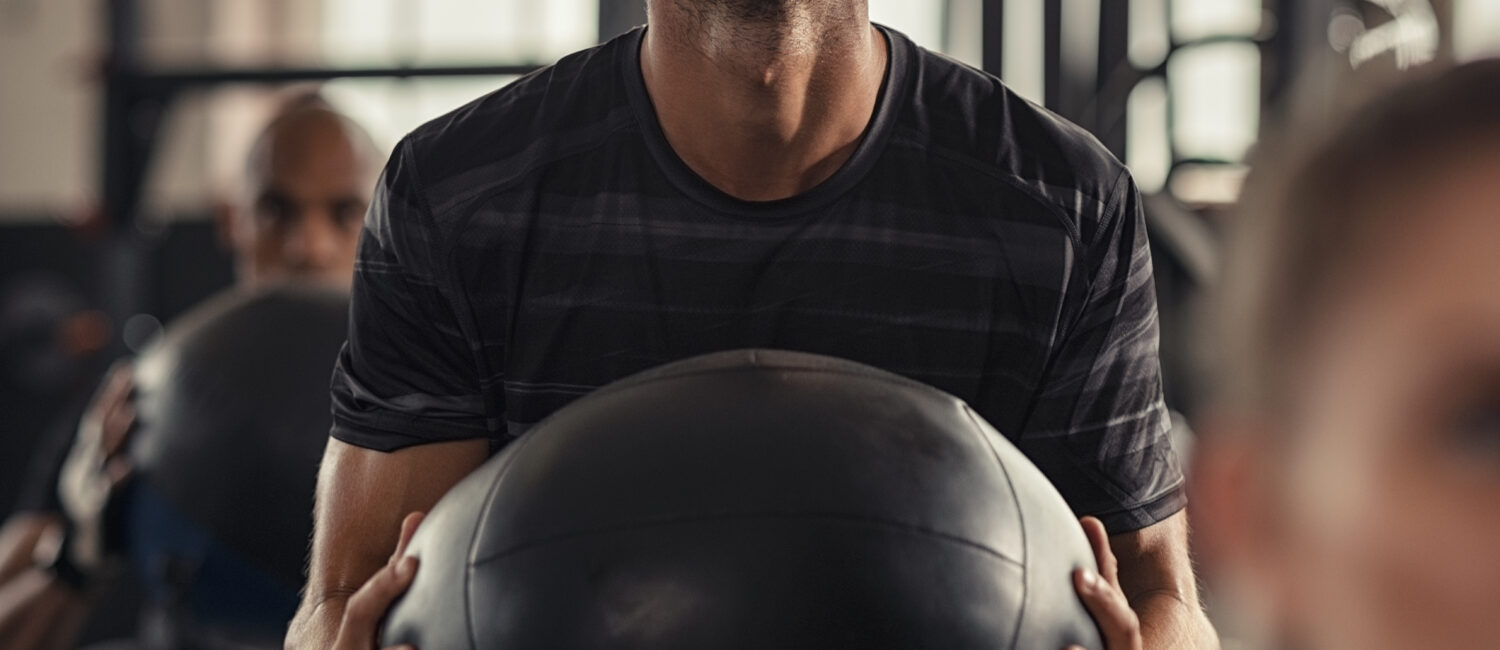 Closeup of sportsman doing weight lifting with heavy medicine ball. Determined man doing cross training training in fitness center. Young man doing intensive squat workout at gym with fitness ball.