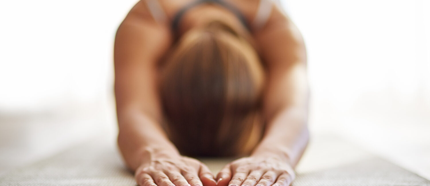 Shot of a young woman practicing yoga