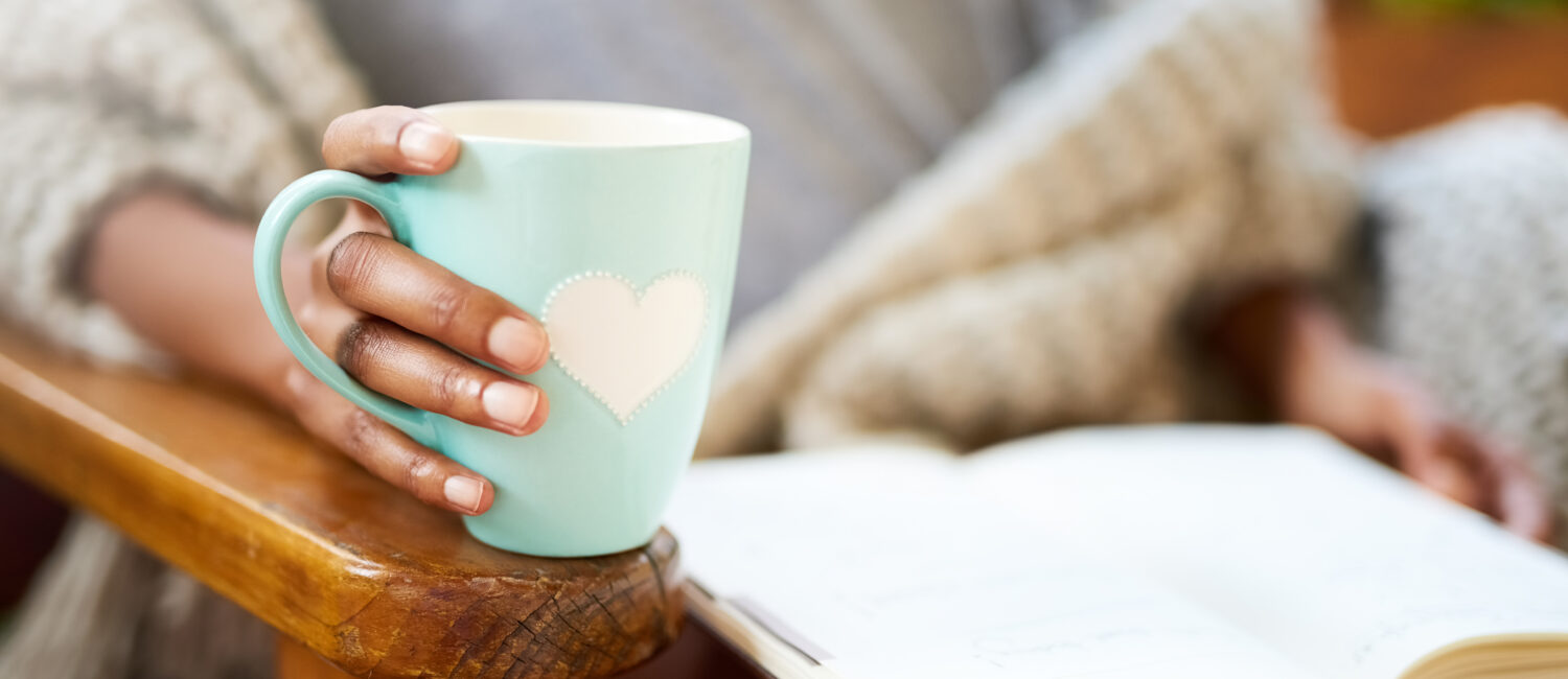 Cropped shot of a woman relaxing with a book and a cup of coffee