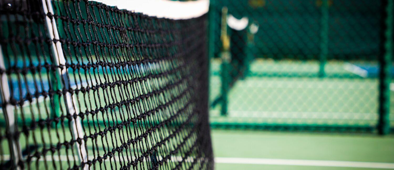Close up of a net on an outdoor pickleball court.