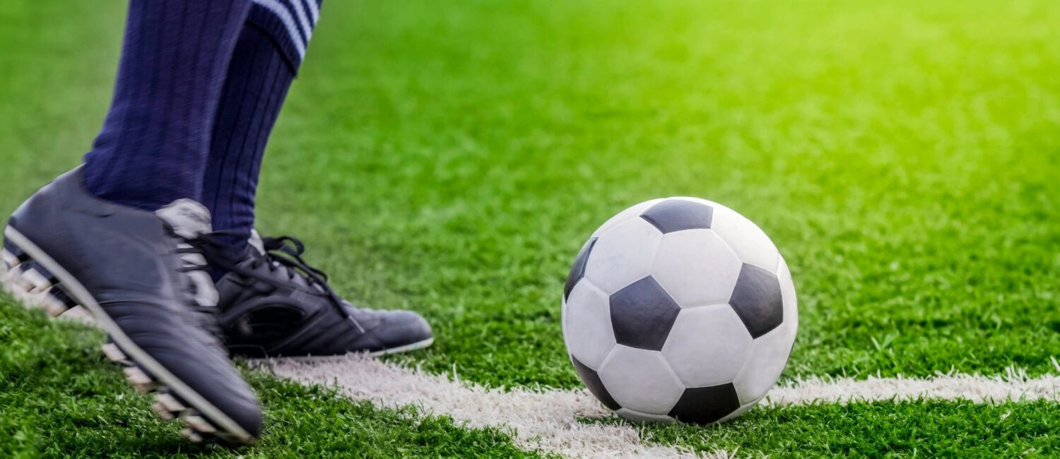 Cropped shot of a teen wearing soccer cleats standing next to a soccer ball on a grass playing field.
