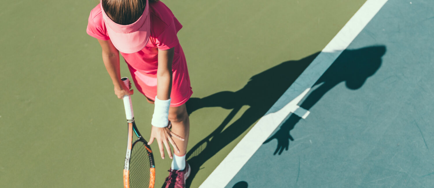 Young girl playing tennis, preparing to serve